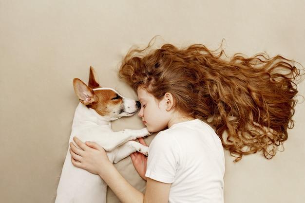 De zoete krullende meisje en jack russell hond slaapt in nacht.
