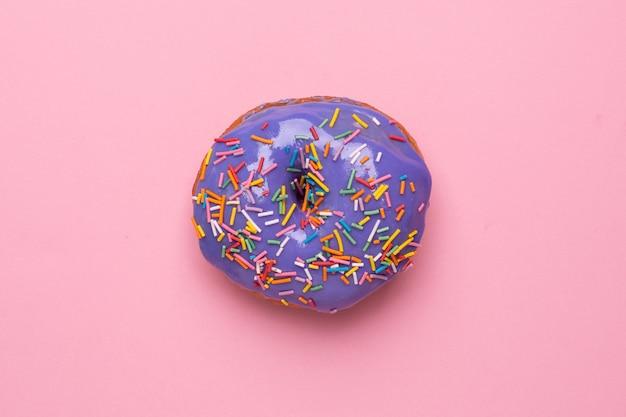 De zoete lilac doughnut met heemst op een roze vlakte als achtergrond lag