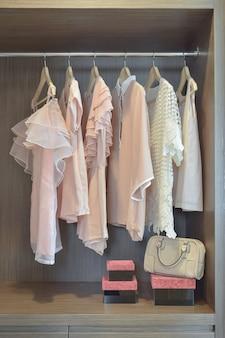 De zoete pastelkleurblouses hangen in open houten garderobe