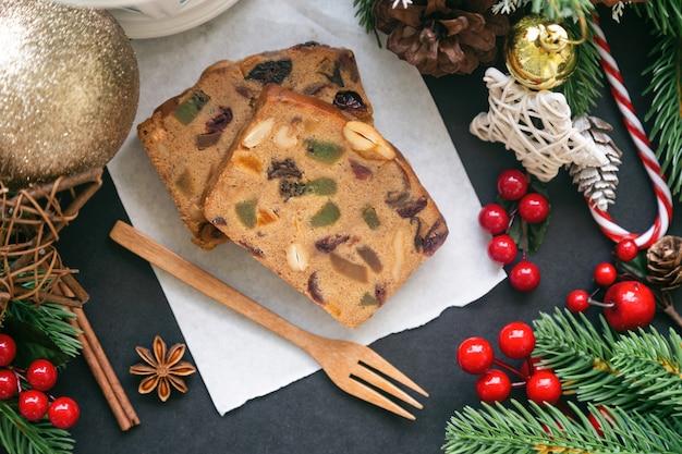 De zoete plakjes van de fruitcake op witboek gezet op zwarte granietlijst in hoogste meningsvlakte leggen met kerstmisdecoratie