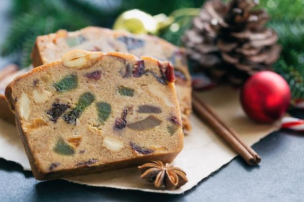 De zoete plakken van de fruitcake op pakpapier zetten op zwarte granietlijst in dichte omhooggaande mening met kerstmisdecoratie.