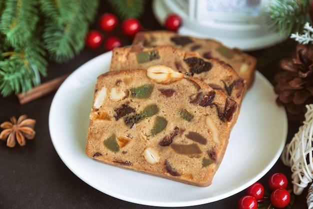 De zoete plakken van de fruitcake op witte plaat zetten op zwarte granietlijst in zijaanzicht met kerstmisdecoratie.