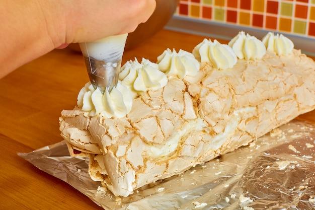 De zoete rol ligt op de folie, de hand van de kok knijpt er een witte crème overheen uit de kookzak