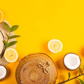 De zomer heldere gele achtergrond met een strozak, hoed, sinaasappelen, citroen, kokosnoot en een groene tak