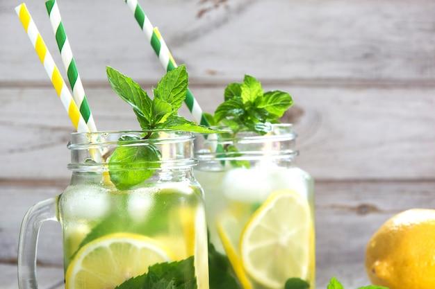 De zomer verfrissend water met citroen, munt en ijs in metselaarkruik op een witte houten achtergrond.