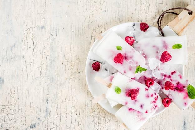 De zomer zoete desserts, eigengemaakte organische roomijsijslollys van framboos en yoghurt, lichtbeige achtergrond