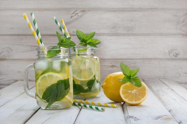 De zomerdrank met citroen, ijs en munt in metselaarkruik op een witte houten achtergrond.