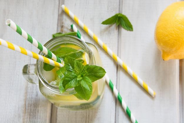 De zomerdrank, water detox met citroen, ijs en munt in metselaarkruik op een witte houten achtergrond.