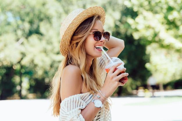 De zomerfoto van mooie vrolijke vrouw in zonnebril, die een verse cocktail van stro drinken