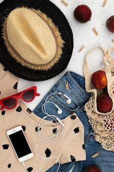 De zomerkleding en accessoires van vrouwen op grijze achtergrond