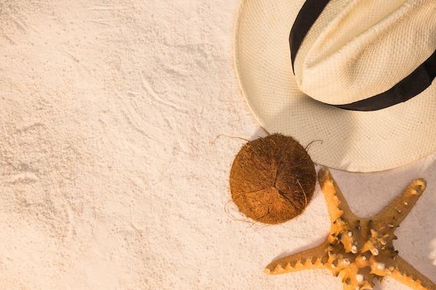 De zomerlay-out van hoedenkokosnoot en zeester op zand