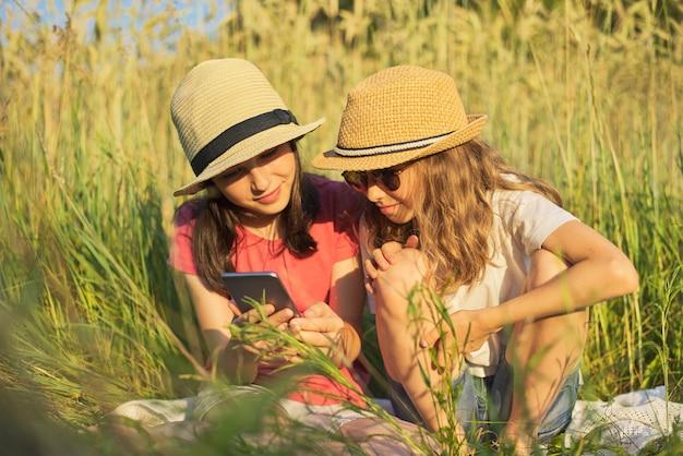 De zomerportret van twee meisjes die in gras zitten