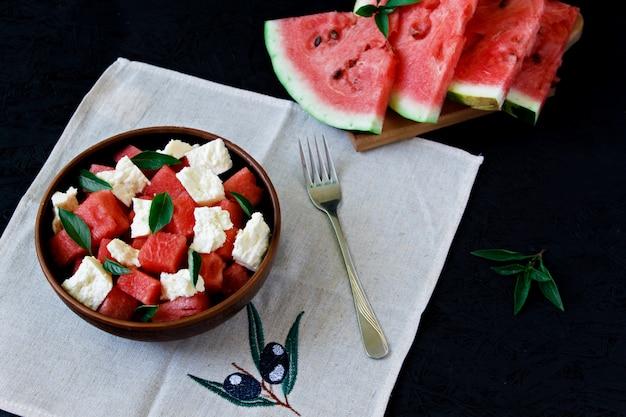 De zomersalade met watermeloen, witte kaas en basilicum in een kleiplaat op een zwarte achtergrond