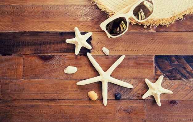 De zomersamenstelling met toebehoren en zeesterren en shells op houten lijst