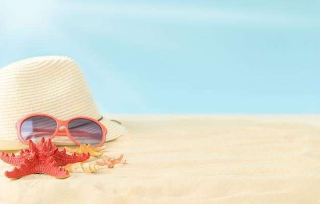 De zomersamenstelling van zonnig strand met zonnebril van de de zonneschijnhoed van de hemel en zeesterren op het zand
