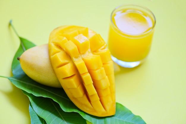 De zomersap van de mango in glas met zoete rijpe plak van mango op groene bladeren van boom tropisch fruit