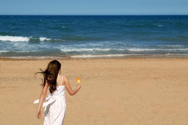 De zomerstrand dat van het tienermeisje met roomijs loopt