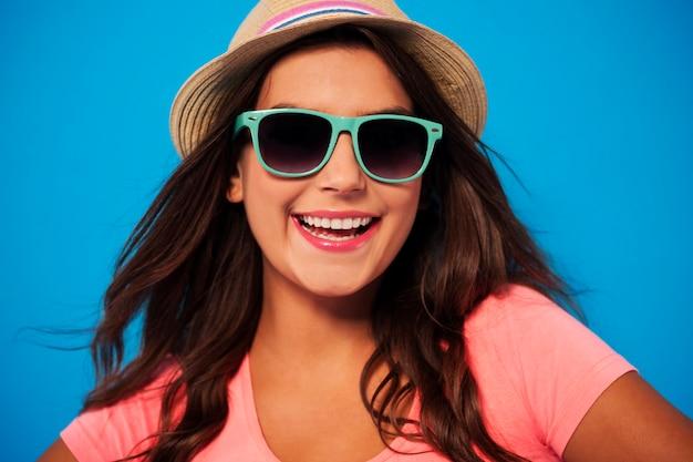 De zomervrouw die zonnebril en strohoed draagt