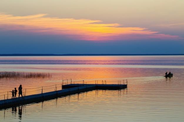 De zomerzonsondergang op de familie en de boot van het meerverstand