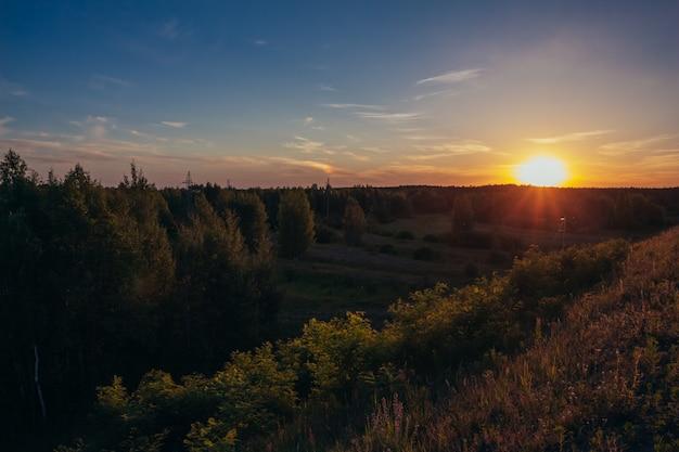De zomerzonsondergang op de horizon achter het bos