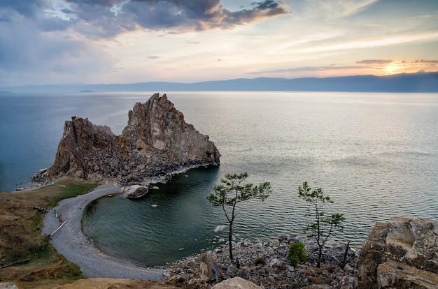 De zomerzonsondergang over rots van shamanka burhan op olkhon-eiland in meer baikal, rusland