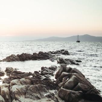 De zon gaat naar beneden over de zee en de zwarte rotsen ervoor