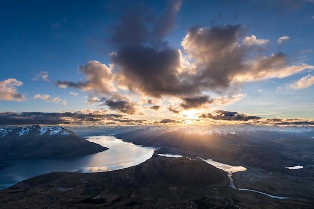 De zon gaat onder boven de zuidelijke alpen, lake wakatipu en frankton arm, queenstown, nieuw-zeeland
