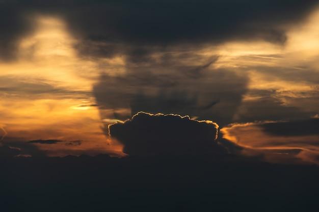 De zon gaat onder een grote wolk naar beneden en geeft een prachtig licht en schaduw