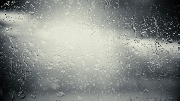 De zon in de wolken schijnt door het glas in de regendruppels. zwart-wit afbeelding