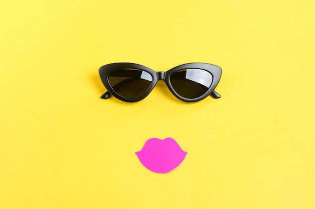 De zon met stijlvolle zwarte zonnebril, roze lippen op geel plat lag