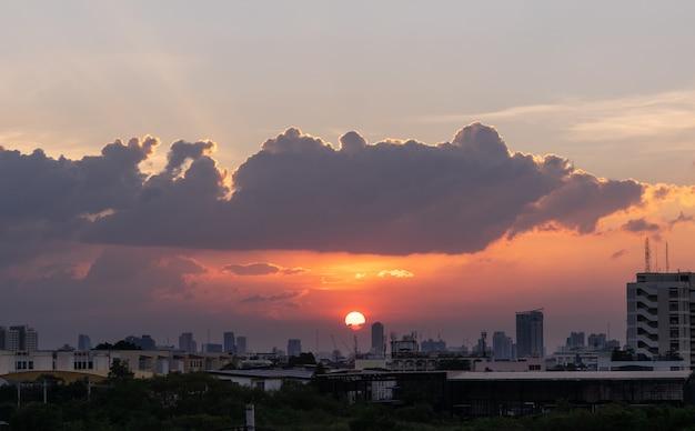 De zon ondergaat in stad met dramatische schemeringhemel op achtergrond