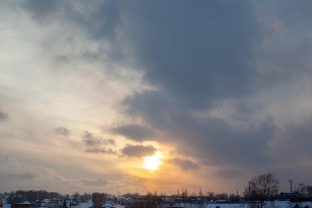 De zon tussen de wolken boven de winterstad.