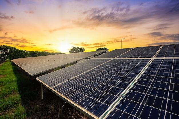 De zonnepaneelcel op de dramatische achtergrond van de zonsonderganghemel, maakt het concept van de alternatieve machtsenergie schoon.