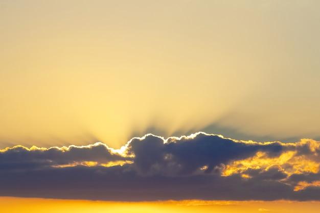 De zonnestralen dringen door donkere wolk bij zonsondergang