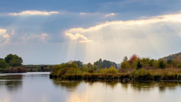 De zonnestralen dringen in de herfst door de wolken boven de rivier