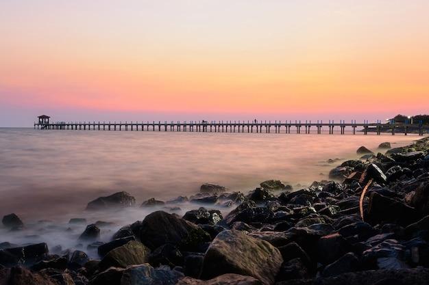 De zonsondergang en de brug midden op zee met geliefden