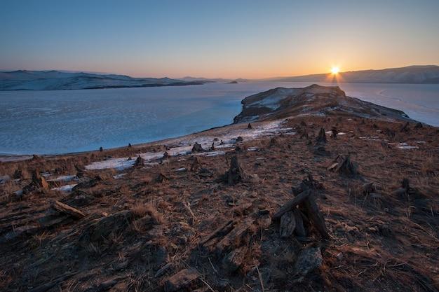 De zonsondergangen over de bergen op de winter het baikalmeer