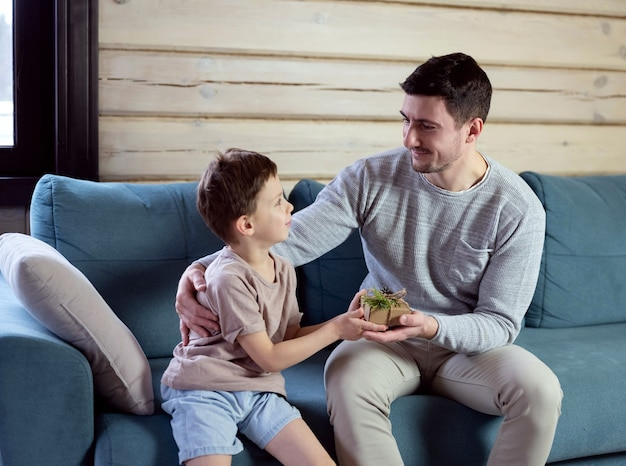 De zoon geeft een cadeau aan papa. vader en zonen op een blauwe bank in een houten huis. kinderen wensen hun vader een gelukkig nieuwjaar.