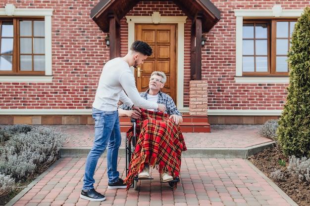 De zoon helpt zijn vader op rolstoel in de buurt van verpleeghuis