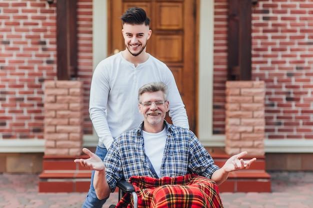 De zoon loopt met zijn vader op rolstoel in de buurt van verpleeghuis