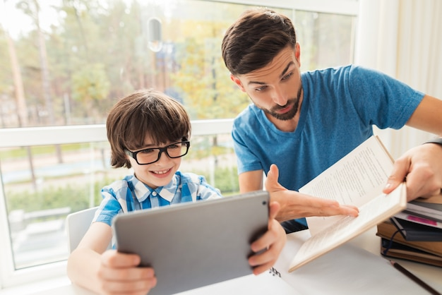 De zoon speelt op de tablet en vader die hem laat zien.
