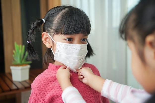 De zus helpt het jongere meisje het chirurgische masker op te zetten. preventie van infectie met coronavirus of covid-19-infectie