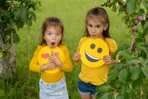 De zussen houden de gezichten van vrolijke emoticons in hun handen