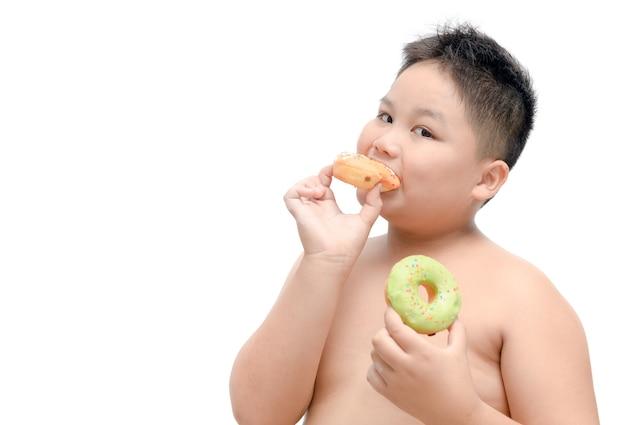 De zwaarlijvige dikke jongen eet geïsoleerde doughnut