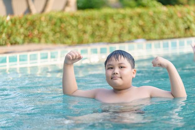 De zwaarlijvige dikke jongen toont spier in zwembad