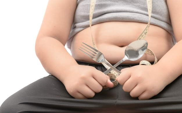 De zwaarlijvige vette geïsoleerde vork en de lepel van de jongensholding