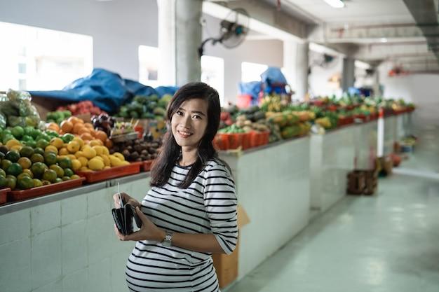De zwangere aziatische vrouw neemt geld uit zijn portefeuille om voor goederen te betalen