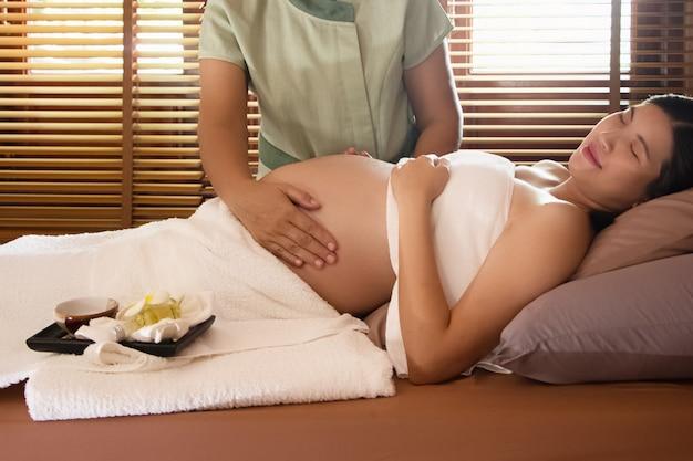 De zwangere vrouw die op bed lag, was massage