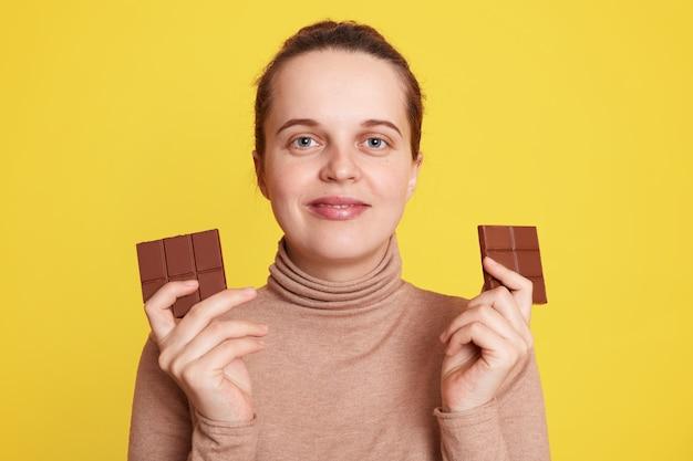De zwangere vrouw die twee repen chocolade in beide handen houdt en direct met tevreden gelaatsuitdrukking kijkt, poseren geïsoleerd over gele muur, wil junkfood eten.