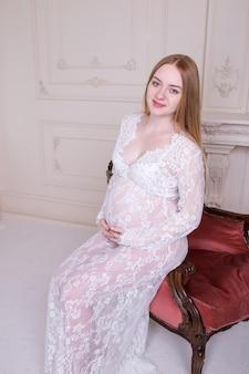 De zwangere vrouw in leunstoel met haar overhandigt buik